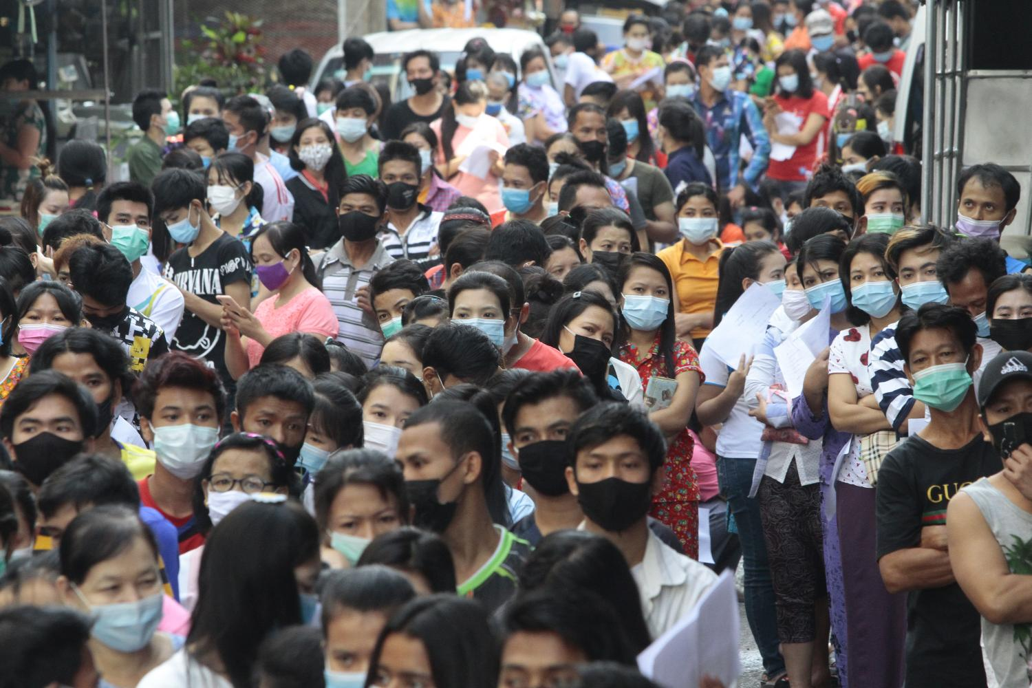 Thousands of migrant workers wait for Covid-19 testing in the wake of a Covid outbreak in Samut Sakhon last December.(Photo by Arnun Chonmahatrakool)