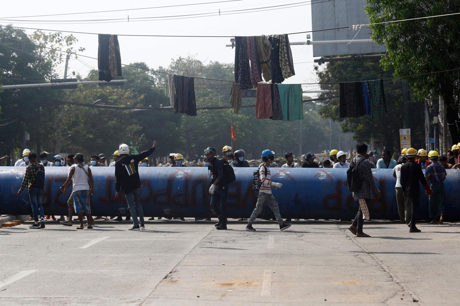 Protesters stand by a large pipe set up to build a barricade as they take part in a demonstration against the military coup in Yangon on Thursday.(Photo:AFP)