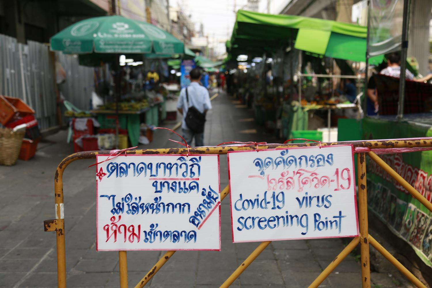 Warning signs at a screening point at a market in Bangkok's Bang Khae district urge visitors to wear masks after a new cluster of infections was detected in the area.