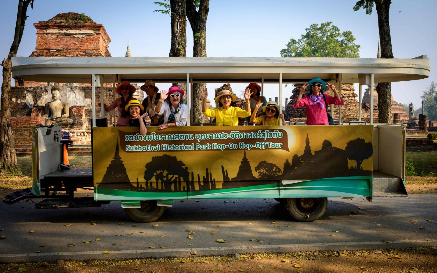 Tourists wave from an electric hop-on hop-off tour bus in Sukhothai Historical Park. Thailand's domestic tourism market is expected to resume in the second quarter this year, driven by the Songkran festival in April. AFP