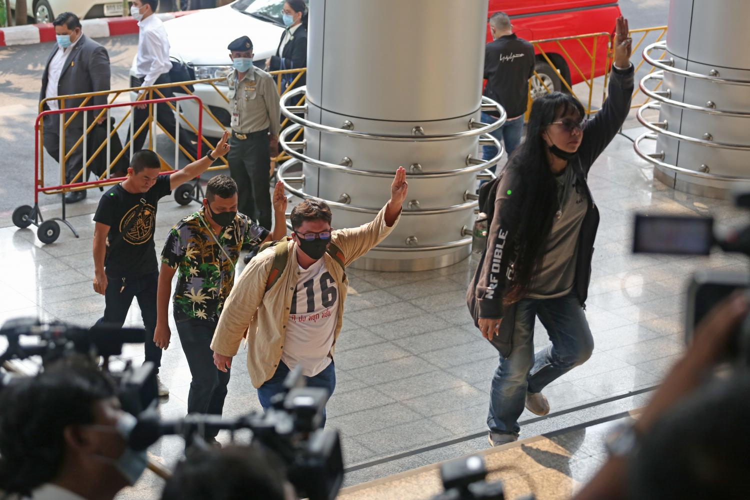 Members of the Ratsadon group flash the three-finger salute as they arrive at the Criminal Court on Ratchadaphisek Road in Bangkok. They were there to attend the court's examination of evidence in the case against several anti-government protest leaders.Varuth Hirunyatheb