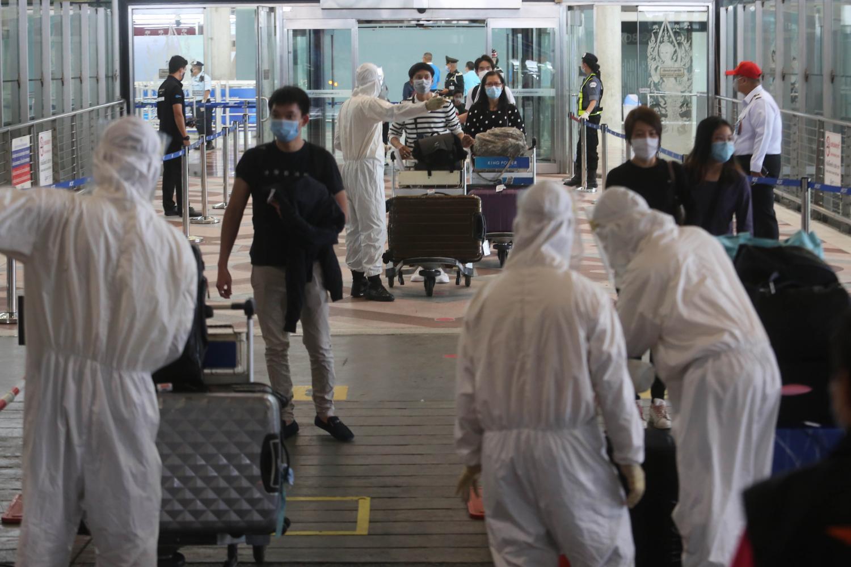 Thai returnees disembarking an Emirates flight are screened for Covid-19 at Suvarnabhumi airport before heading to mandatory quarantine at state quarantine hotels. Wichan Charoenkiatpakul