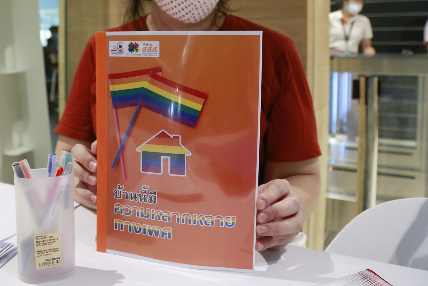 A woman holds up a guidebook designed to help parents of LGBT children overcome challenges and prejudices.Arnun Chonmahatrakool