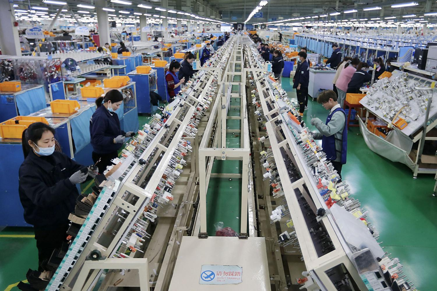 Workers on a wire harness production line at a factory in Huaibei, China in March.(Photo: STR/AFP)