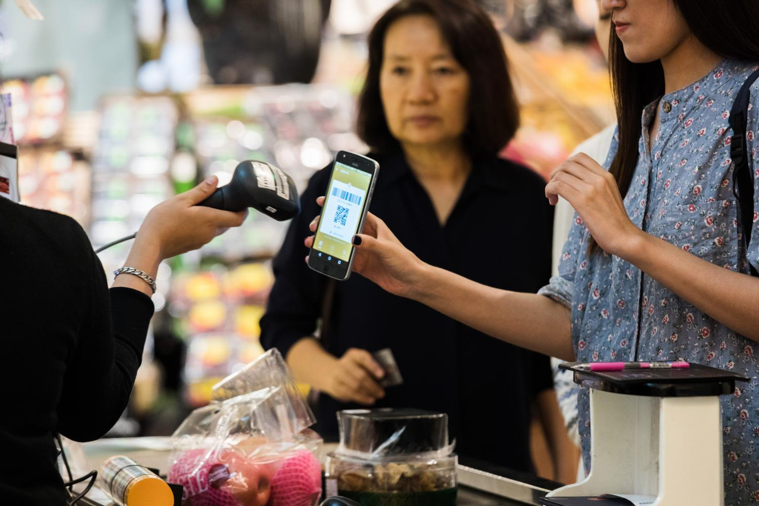 A customer has a QR code scanned from a smartphone at a grocery store in Bangkok.  (Photo: Bloomberg)