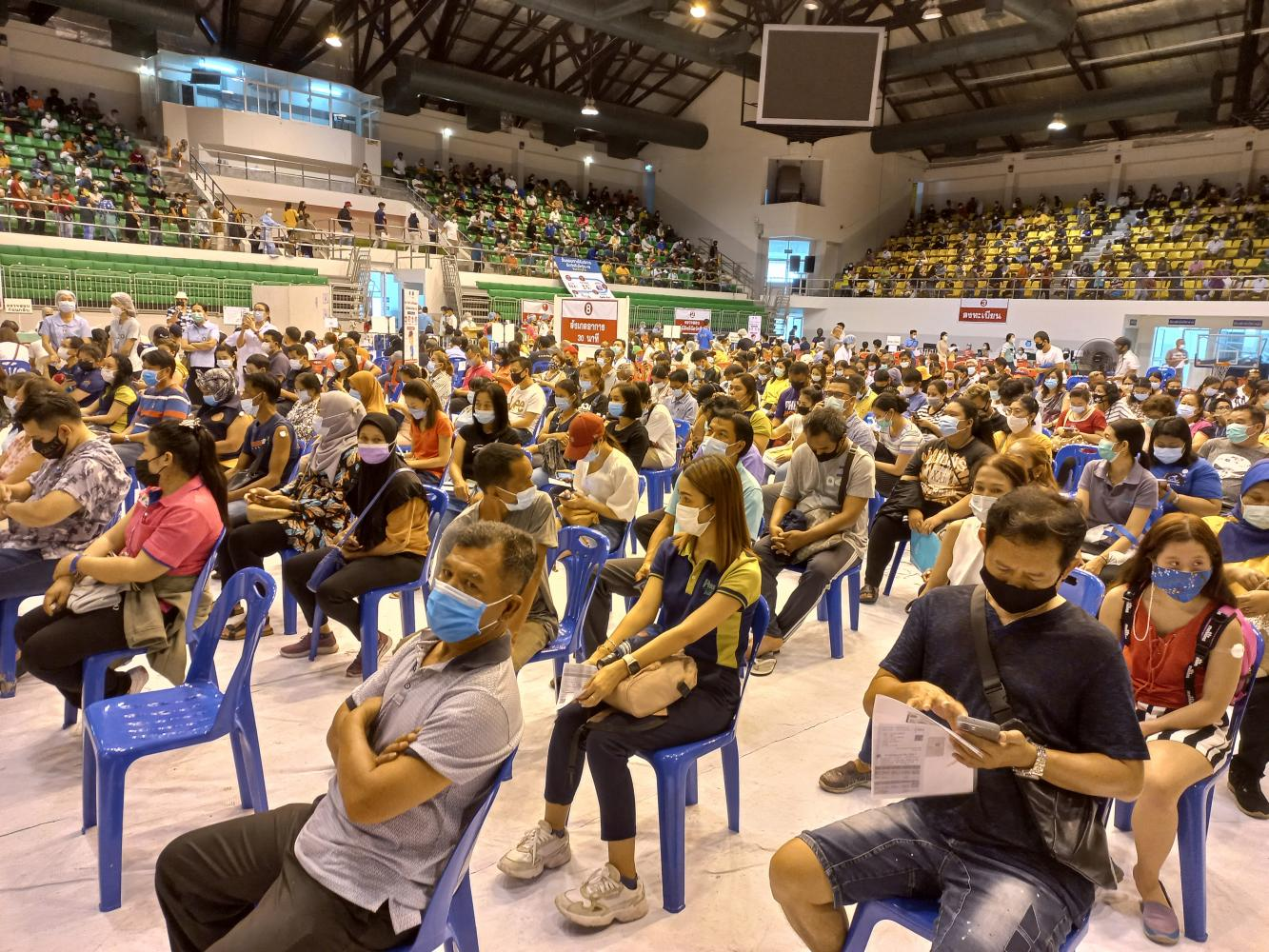 People wait to be vaccinated against Covid-19 at a gymnasium in Saphan Hin, in Phuket. The province is vaccinating local people ahead of reopening to foreign tourists in July. Achadthaya Chuenniran