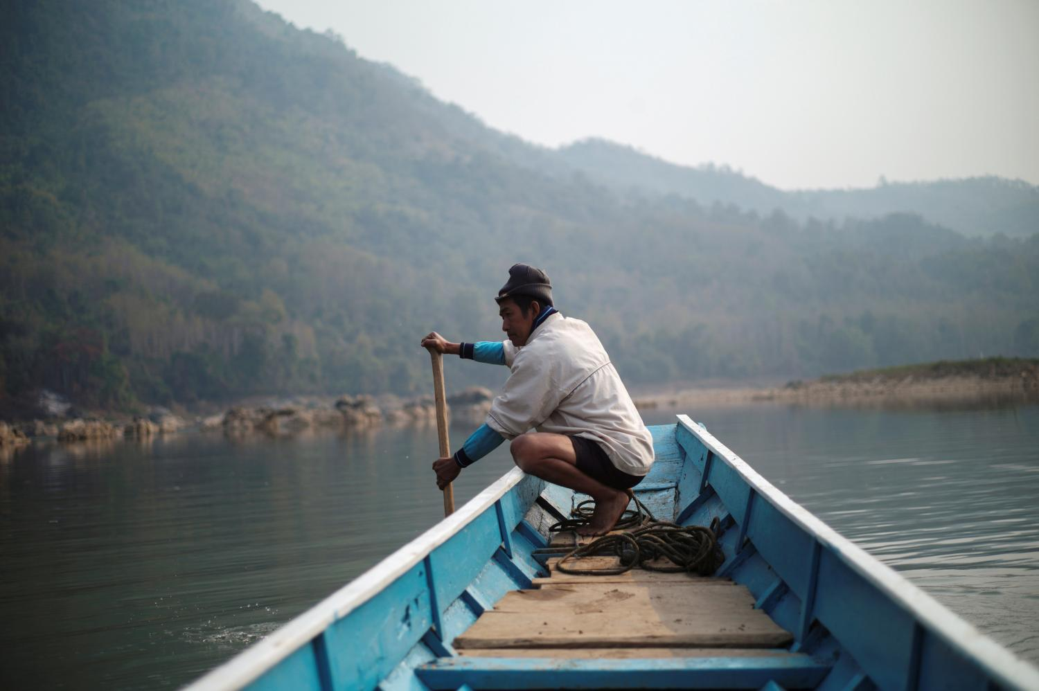In this file photo from February, a villager steers a boat where the future site of the Luang Prabang dam will be on the Mekong River in Laos. The Thai government and corporations are among the most vociferous proponents of dam projects in the country. (Photo: Reuters)