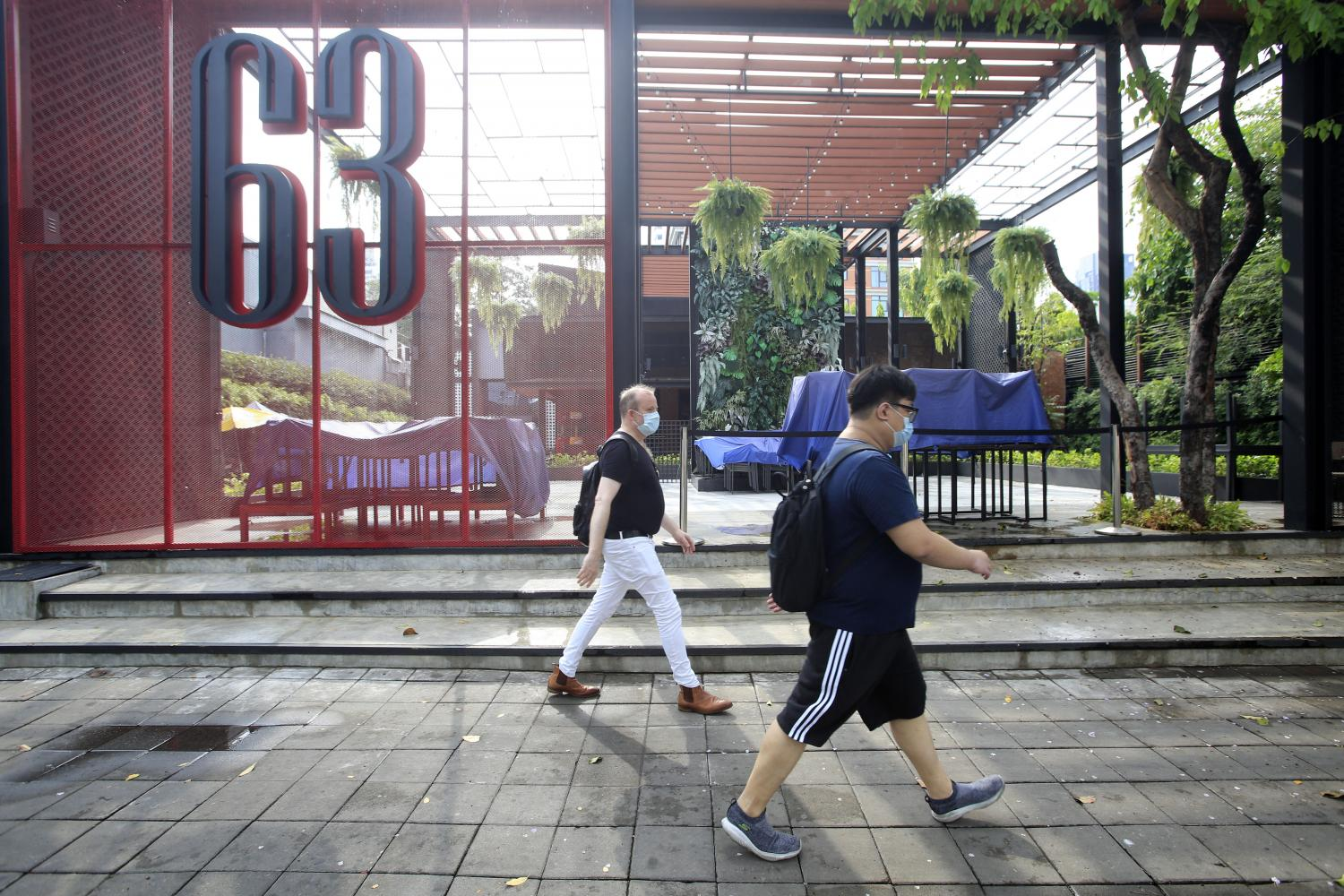 Pedestrians pass by a mothballed entertainment venue. Entertainment venues in the Thong Lor-Ekamai neighbourhood have been ordered to remain closed until April 19. (Photo by Pornprom Satrabhaya)