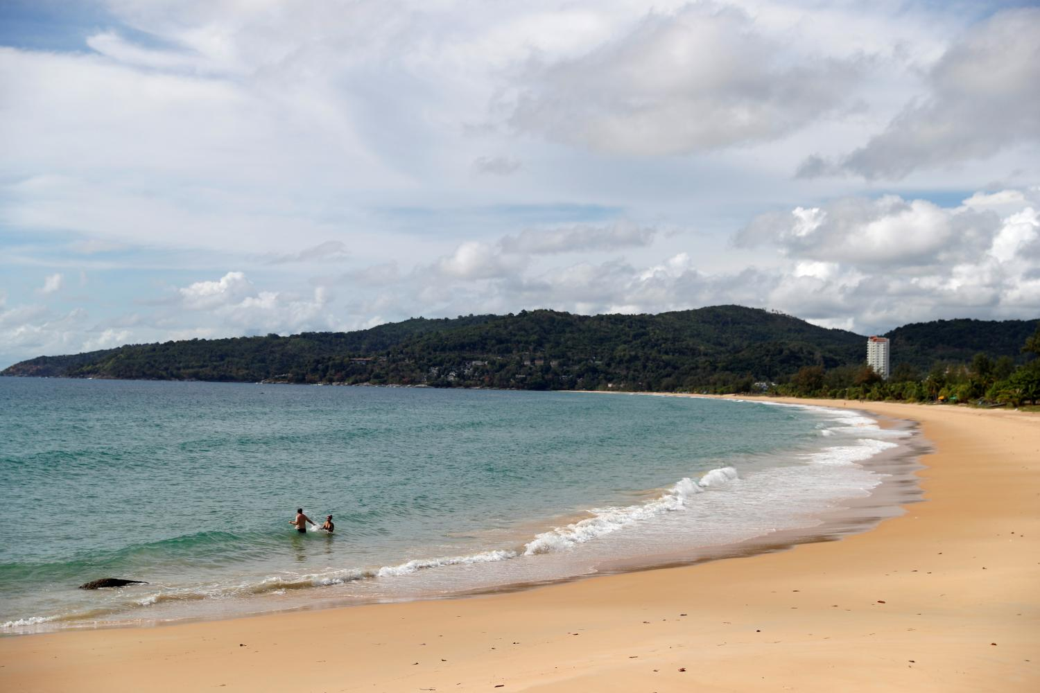 People wade at an empty beach in Phuket last month. (Reuters photo)