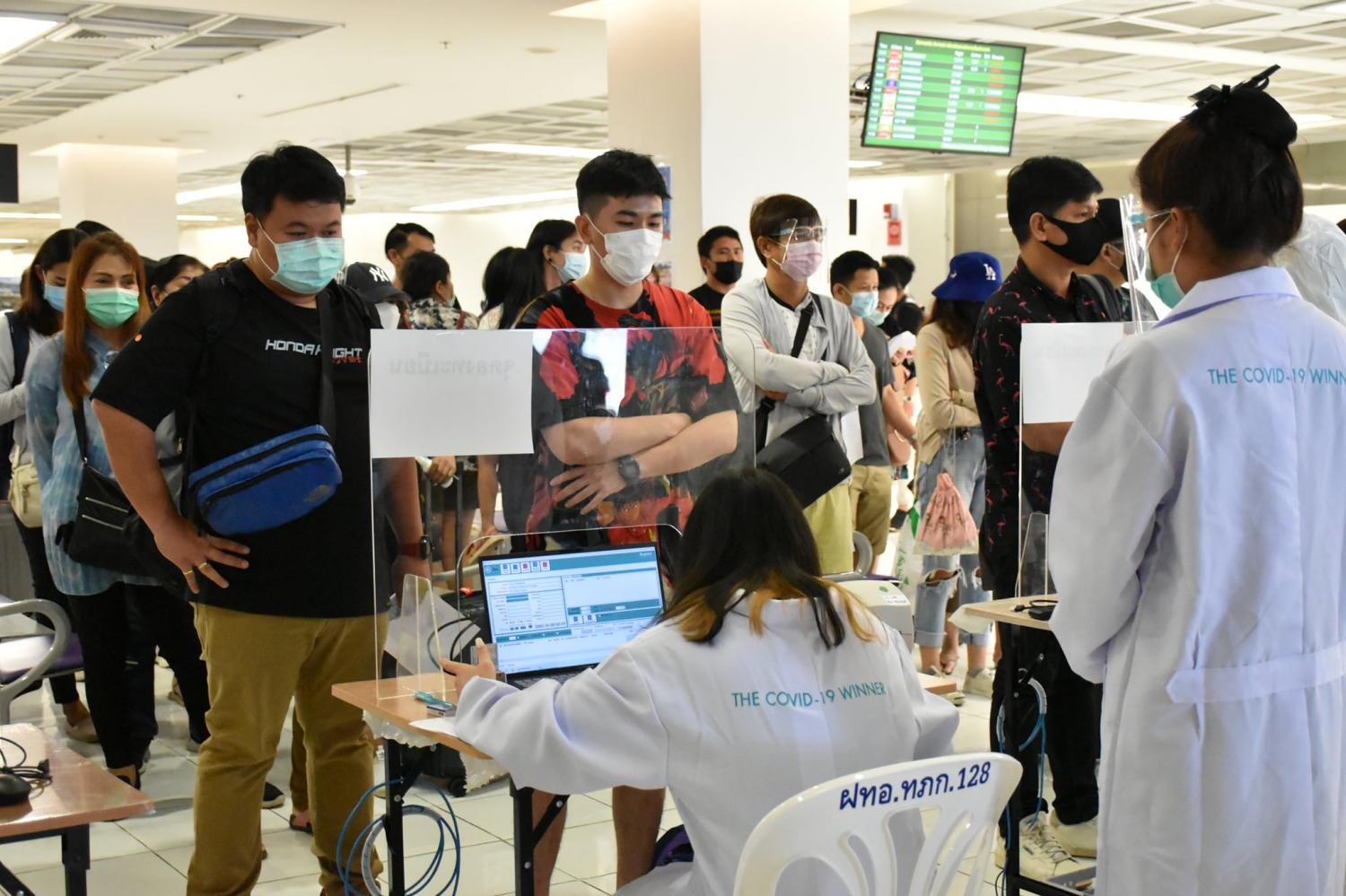 Passengers at Phuket Airport queue up for Covid-19 screening. The island province is imposing thorough checks and restrictions on all arrivals until the end of the month to curb the spread of Covid-19. (Photo by Achadthaya Chuenniran)