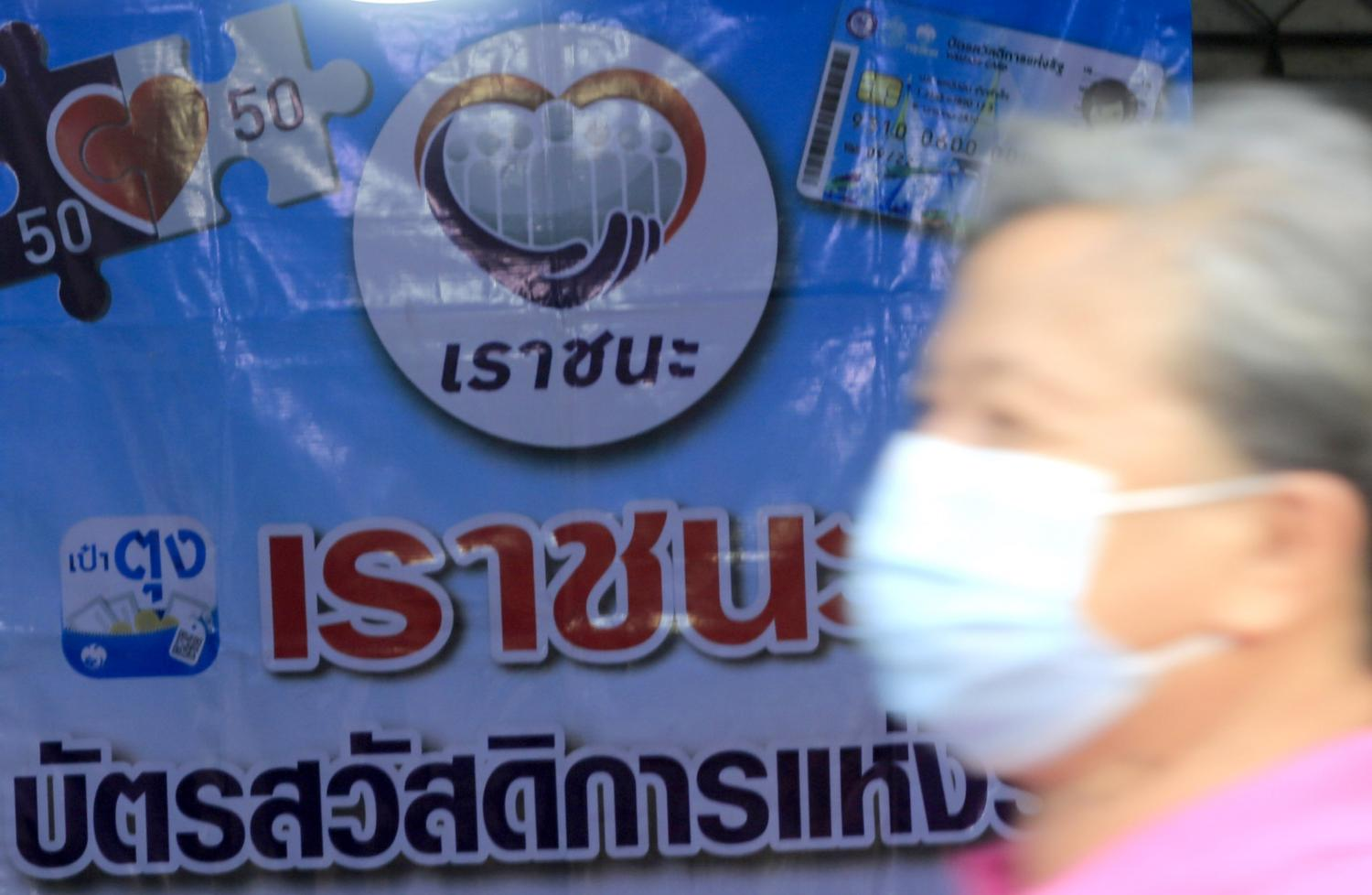 A man wearing a face mask walks past a sign of the Rao Chana (We Win) financial stimulus and the Kon La Krueng (Half-Half) co-payment scheme at Chatuchak weekend market. (Photo by Pornprom Satrabhaya)