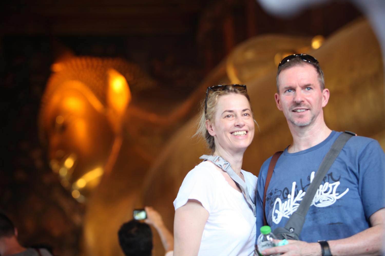 Foreign tourists pose for a photograph at Bangkok's Wat Pho, also known as the Temple of the Reclining Buddha or Wat Phra Chetuphon amid Covid-19.Apichart Jinakul