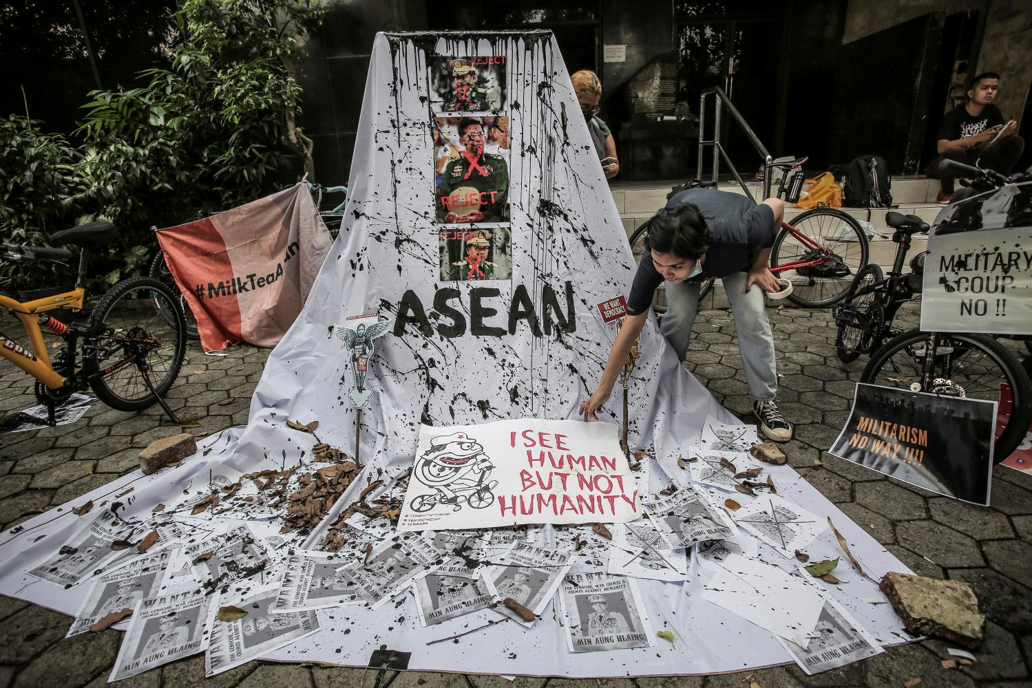 Ahead of the special Asean Summit in Jakarta last Saturday, a woman prepares a placard out of crossed-out portraits of Myanmar's junta chief Senior General Min Aung Hlaing during a protest against the military coup.(Photo: Reuters)
