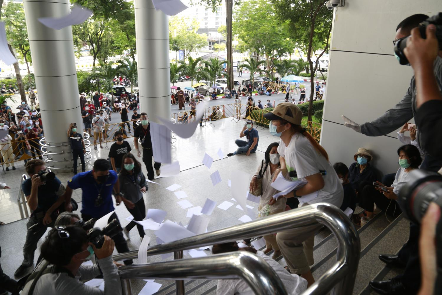 Student activist Benja Apan from the student activist group United Front of Thammasat and Demonstration on Thursday scatters copies of letters demanding the release of seven co-leaders of the Ratsadon group at the Criminal Court on Ratchadaphisek Road after no one from the court came out to receive one. (Photo by Arnun Chonmahatrakool)