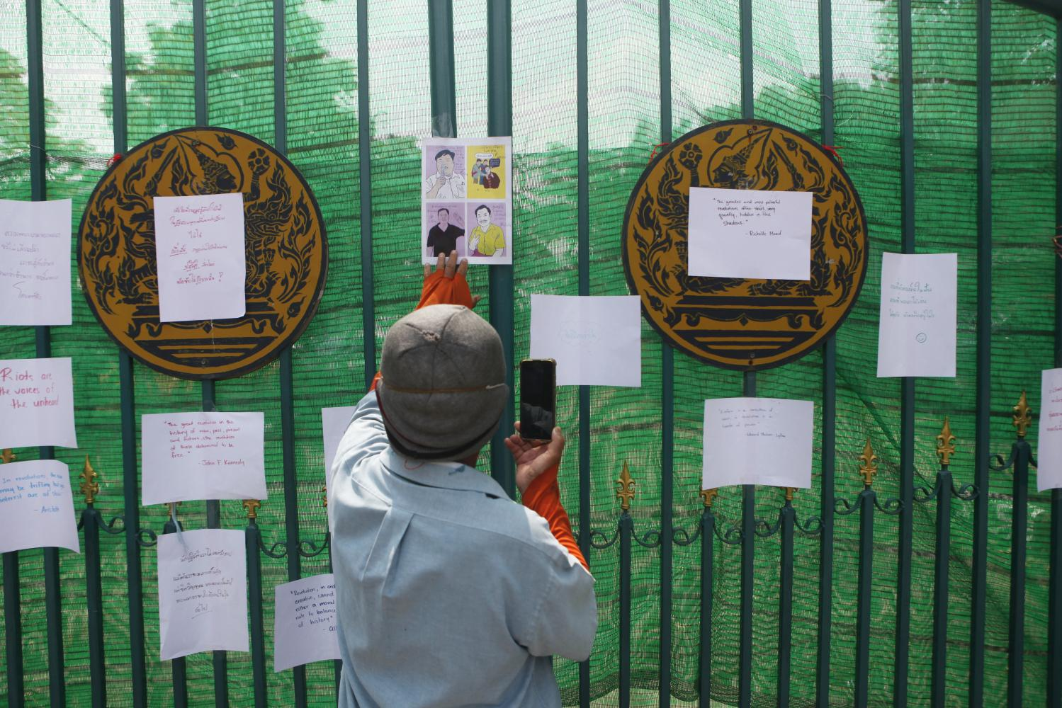A man takes a photo of caricatures of four detained protest leaders, including Parit 'Penguin' Chiwarak, who is reported to been passing bloody stools and has been taken to hospital to be put on an intravenous drip after the 46th day of his hunger strike.(Photo by Nutthawat Wicheanbut)