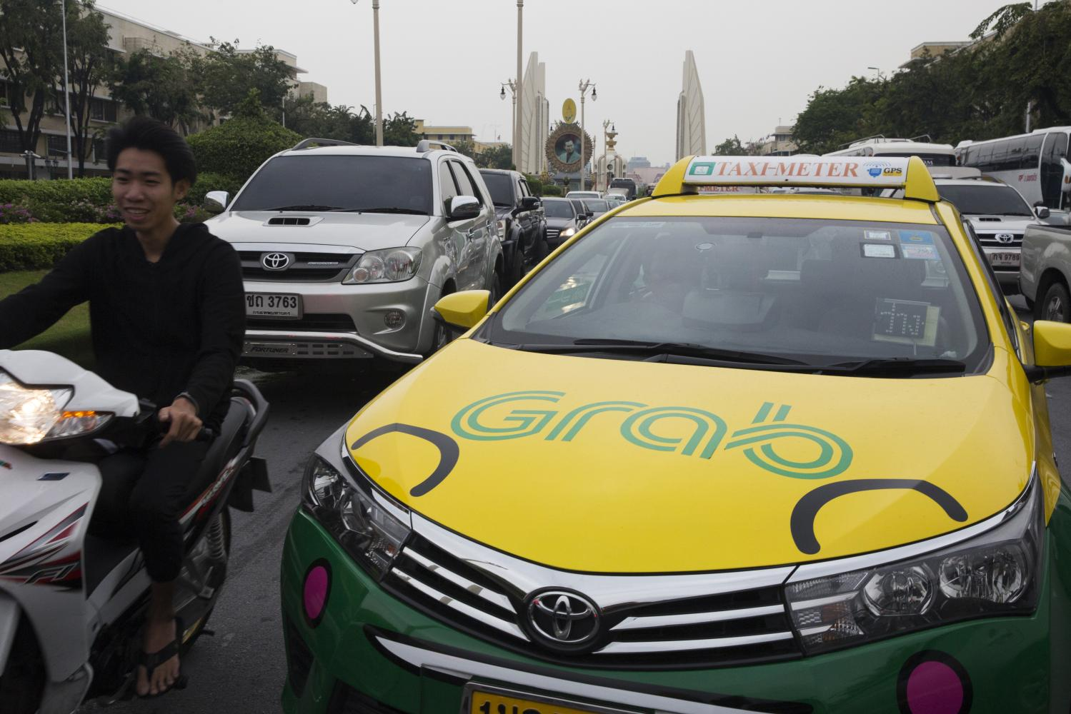 The Grab logo is displayed on a taxi near Democracy Monument in Bangkok. (Photo: Bloomberg)