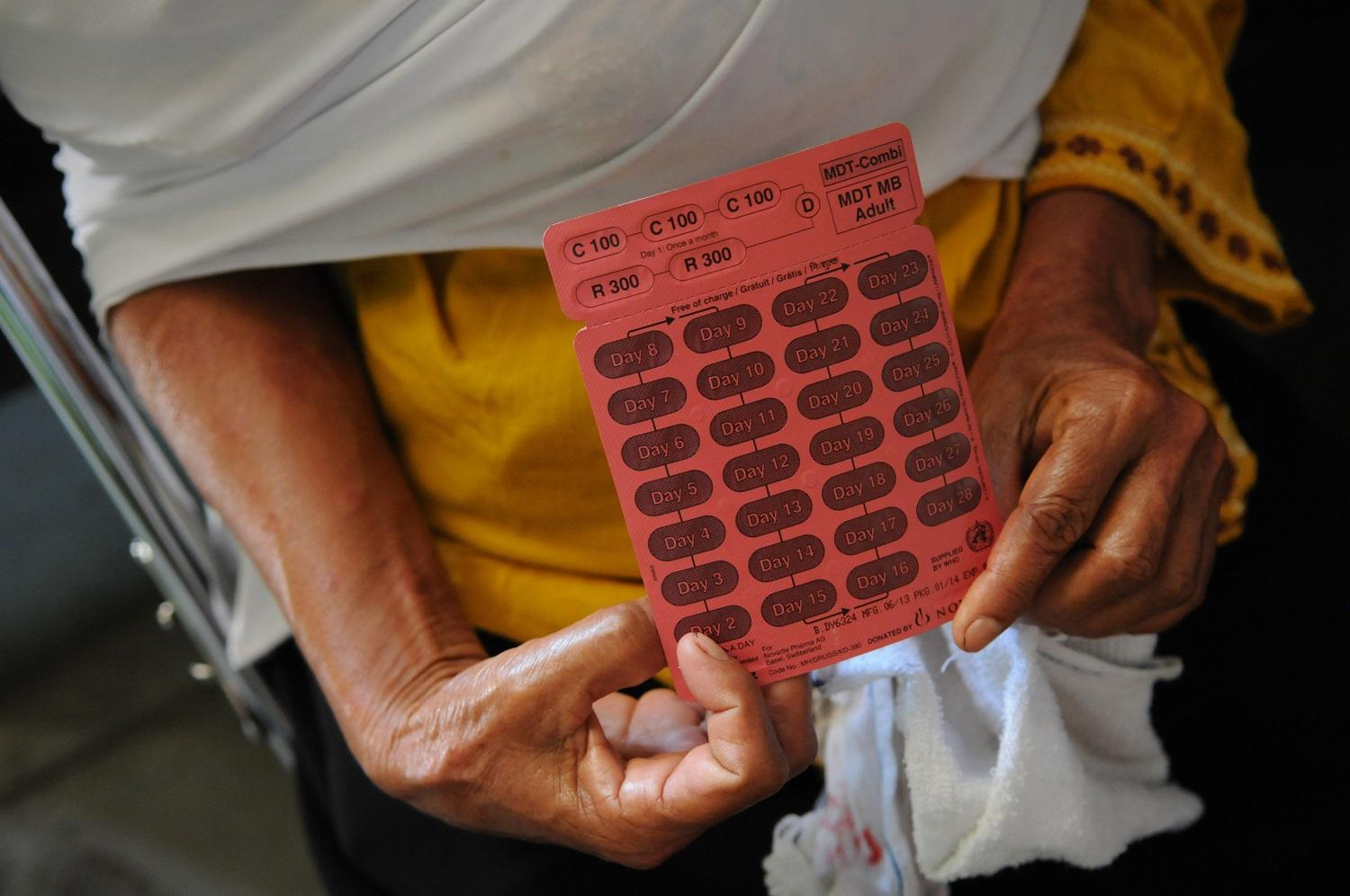 An Indonesian woman affected by leprosy holds up a blister pack of medicine in South Sumatra, Indonesia.(Photo: NLR)