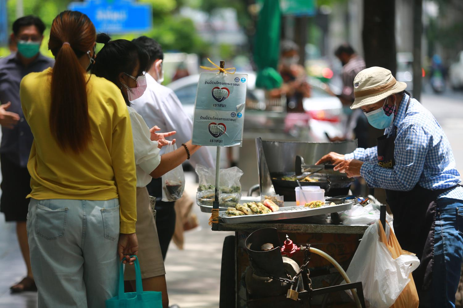 A sign for the Rao Chana (We Win) scheme is seen at a food stall in the Silom area of Bangkok. (Photo by Somchai Poomlard)
