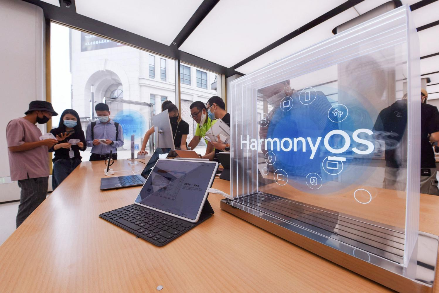 People try Huawei products with the Harmony operating system at a Huawei store in Shanghai on Thursday. (STR/AFP photo)
