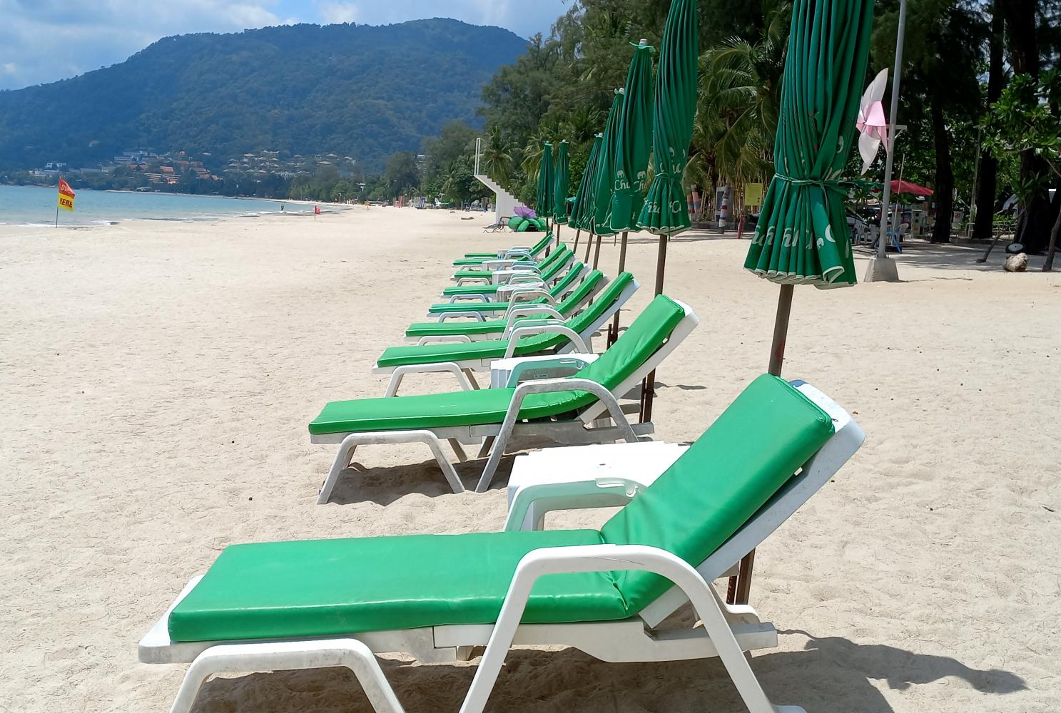 Beach chairs are placed on an empty beach in Phuket as the island province gears up for its July 1 reopening to tourists.(Photo by Achadthaya Chuenniran)