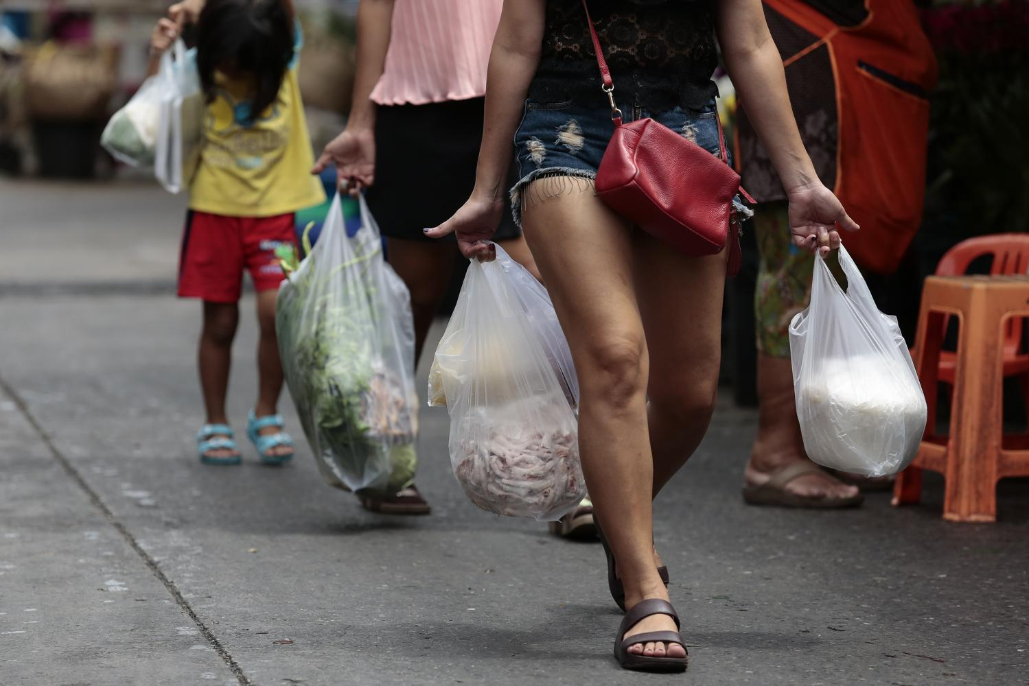 A shopper heads home with plastic bags.Patipat Janthong