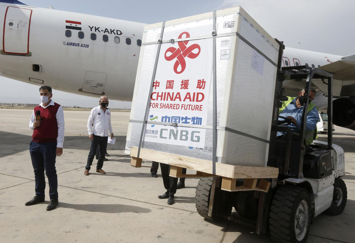Workers unload boxes containing Sinopharm's Covid-19 vaccine, donated by China, at Damascus International Airport in April in the Syrian capital. Vaccine diplomacy can increase mutual respect, benefits and trust among nations.AFP