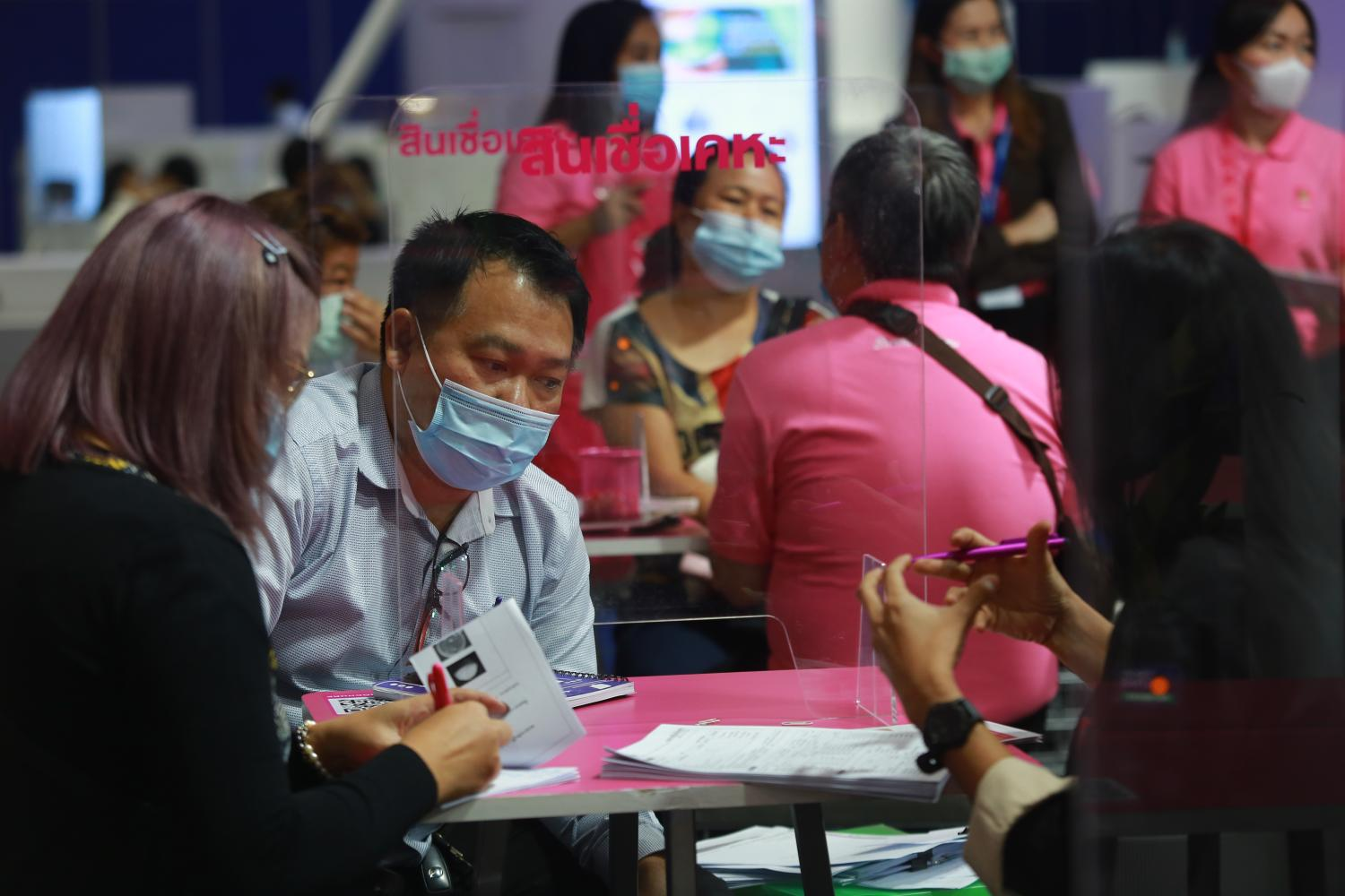 People discuss personal loans at a Money Expo held at Bitec in December. Household debt grew by around 5% in the first quarter this year. (Photo by Somchai Poomlard)