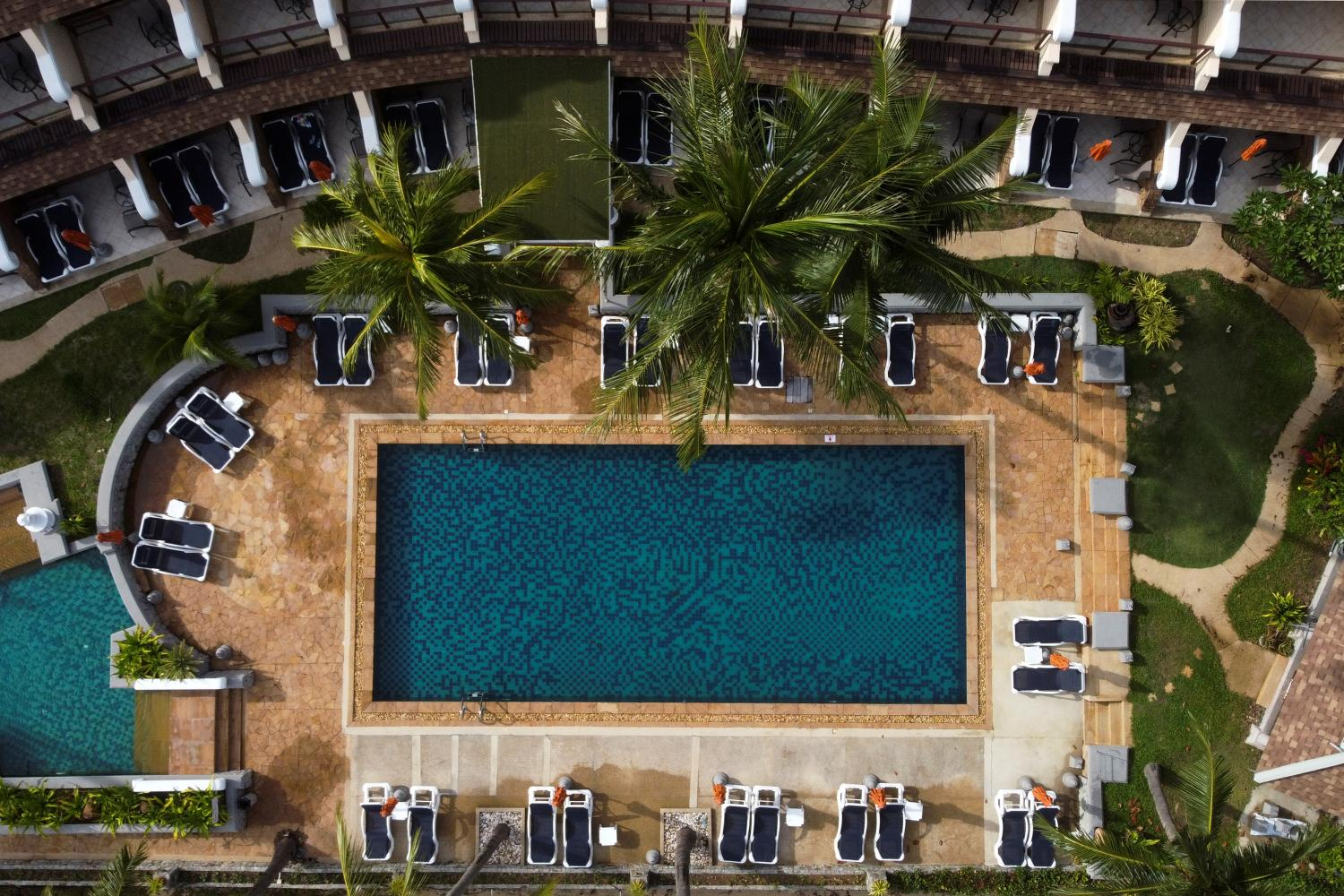 Empty sunbeds are seen around the swimming pool of a hotel which has opened for visitors in Karon, Phuket.(Reuters photo)