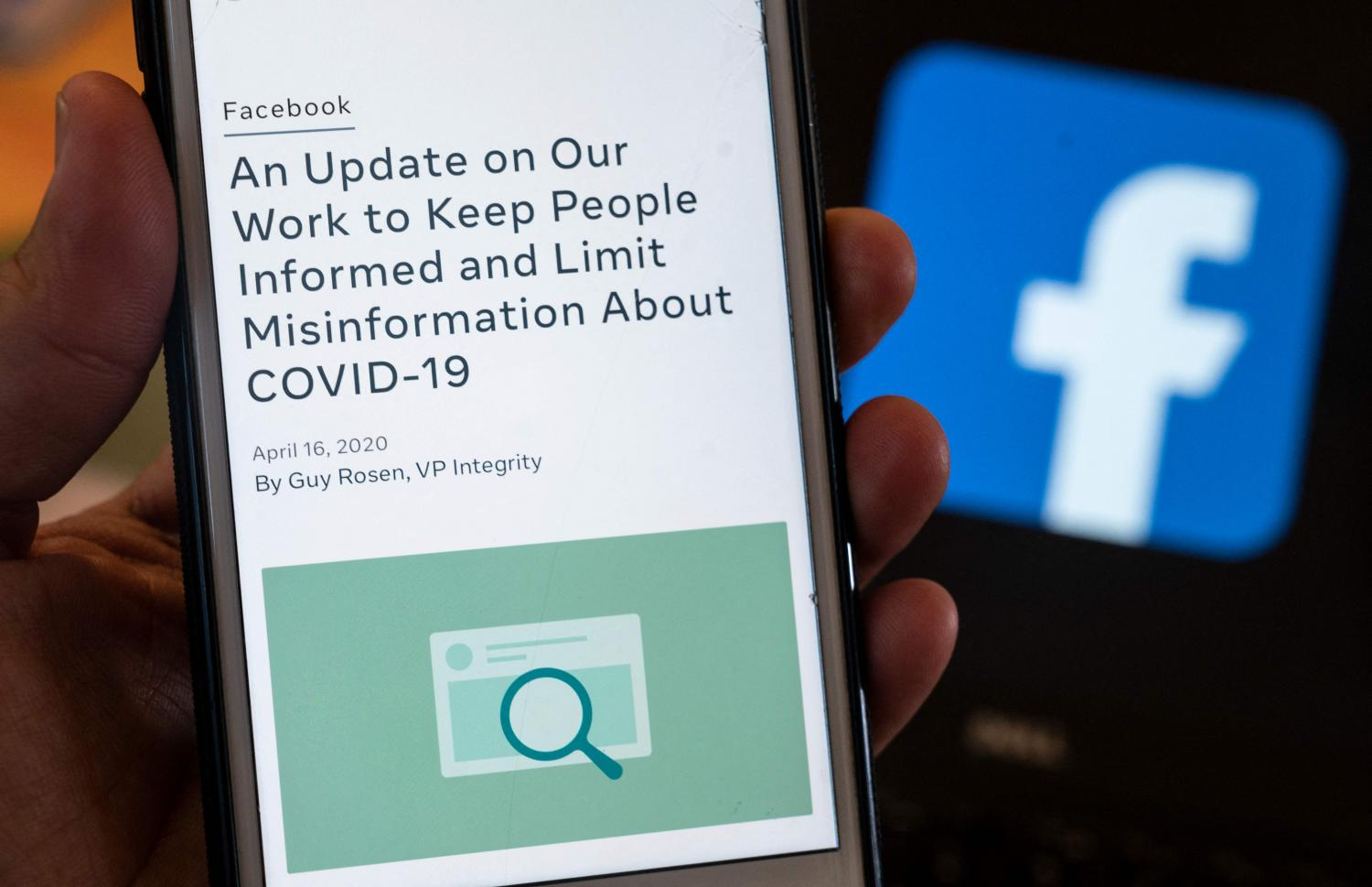 A smart phone screen displays a policy on Covid-19 misinformation. Facebook has reversed its policy banning posts suggesting the Covid-19 was man-made.(AFP photo)