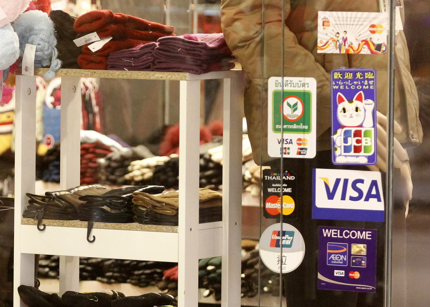 Stickers showing a variety of credit cards accepted are displayed on the door of a shop in Bangkok. Thanarak Khunton