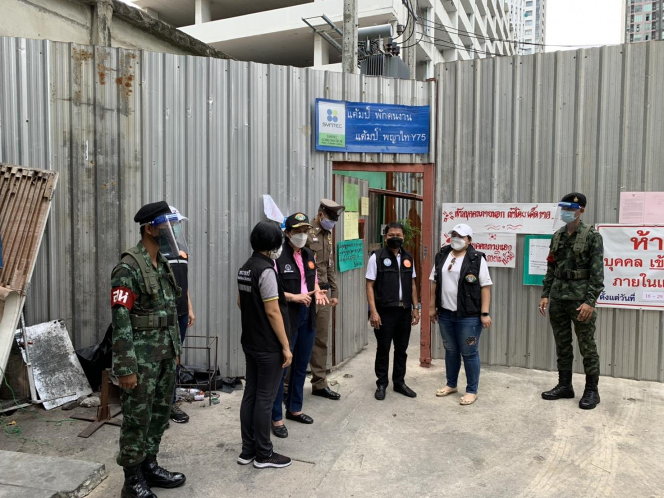 Military police stand guard at the entrance of a construction workers' camp in Bangkok's Phaya Thai district on Saturday to bar workers from leaving the camp. (Royal Thai Army photo)