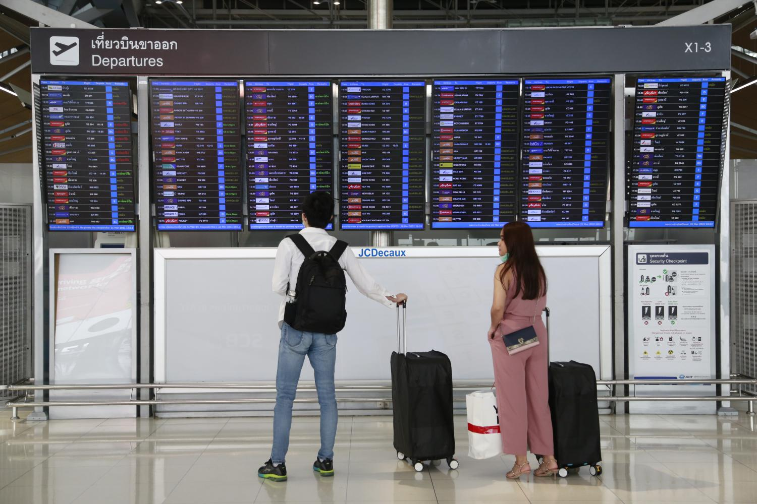 Tourists are seen checking their flights' status at Suvarnabhumi airport amid the Covid-19 pandemic on March 21 this year.Arnun Chonmahatrakool