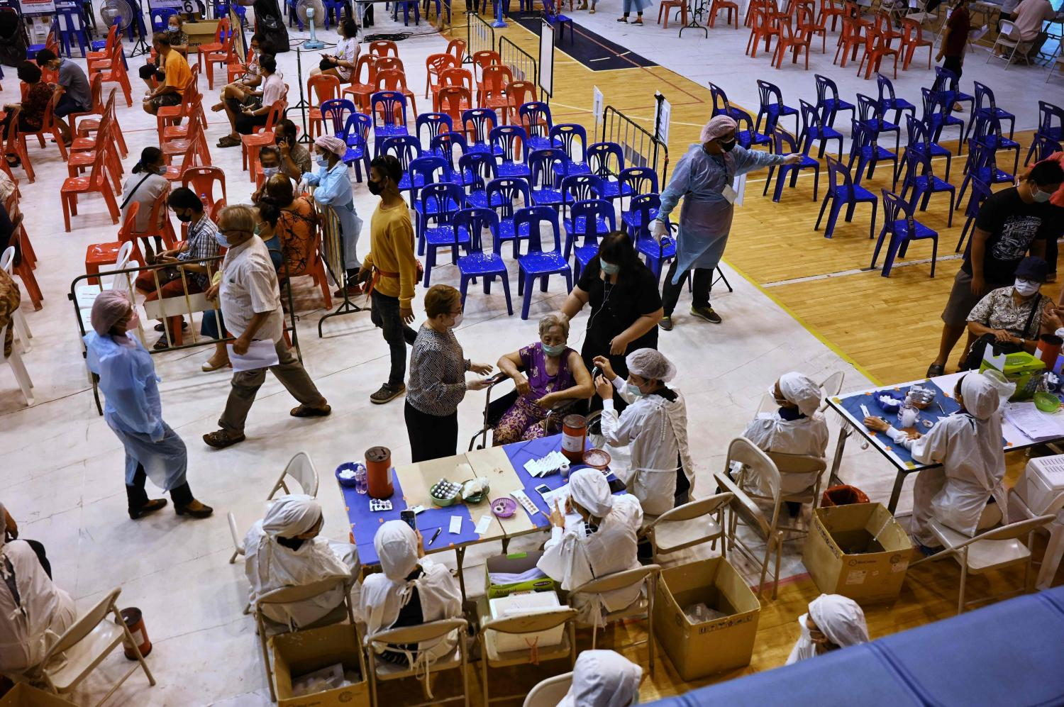 Health workers administer doses of the AstraZeneca vaccine to elderly residents at a sports stadium in Phuket on Tuesday.(AFP photo)