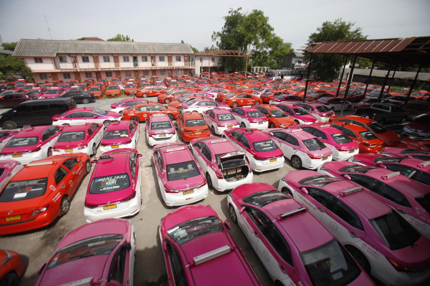 A Bangkok parking lot filled with taxis owned by cooperatives, as 2,000 cars were returned by drivers who cannot afford the rental fees. (Photo: Nutthawat Wicheanbut)