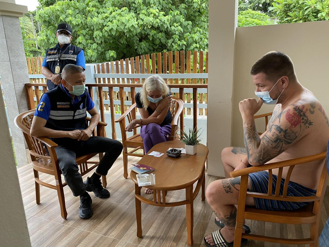 An immigration police officer questions one of two German drug fugitives arrested Tuesday morning. Immigration Bureau photo