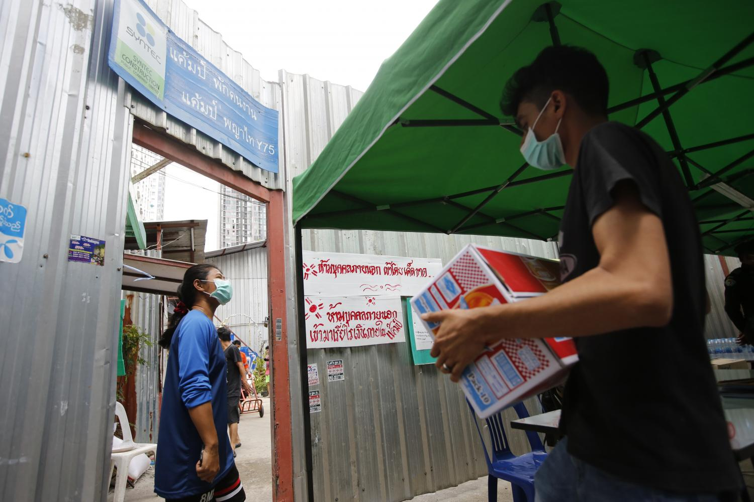 Workers at a construction site on Soi Phetchaburi 7 in Bangkok's Phaya Thai district emerge to pick up delivered food. Construction sites in Bangkok and its vicinity have been closed for one month following the government's semi-lockdown imposed last Thursday.(Photo: Wichan Charoenkiatpakul)