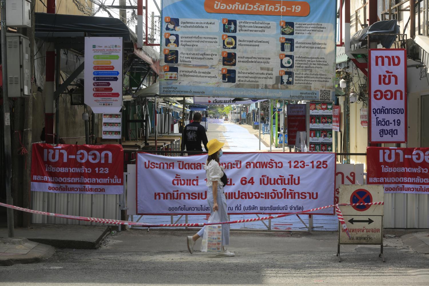 A pedestrian walks past the entrance to Bang Kapi market in Bangkok which recently reopened after being closed temporarily in June.Pornprom Satrabhaya