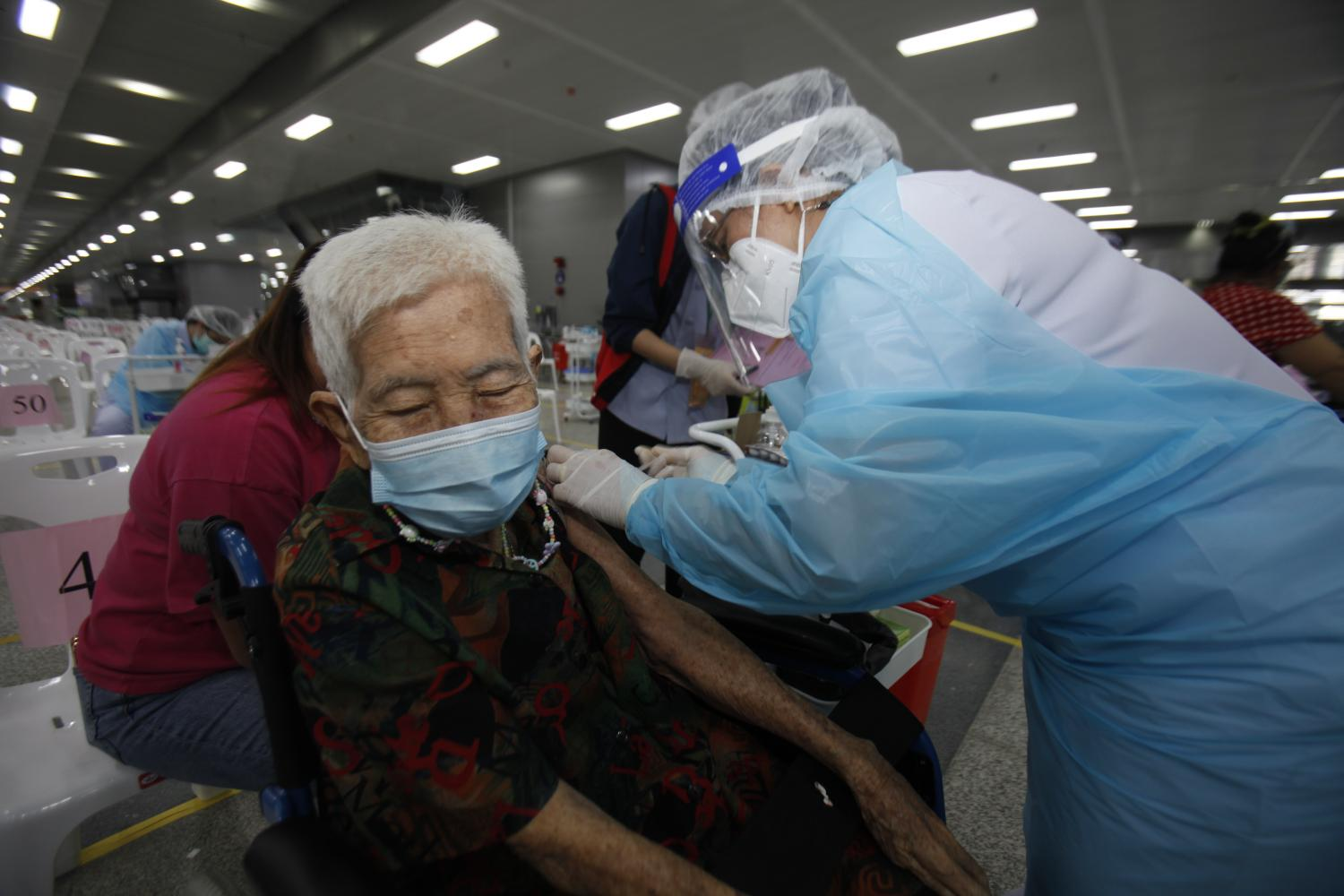 Elderly people flock to Bang Sue Grand Station for Covid-19 shots available for those aged 75 and over. They are allowed one family member or helper each to assist them during the vaccination process.(Photo: Nutthawat Wicheanbut)
