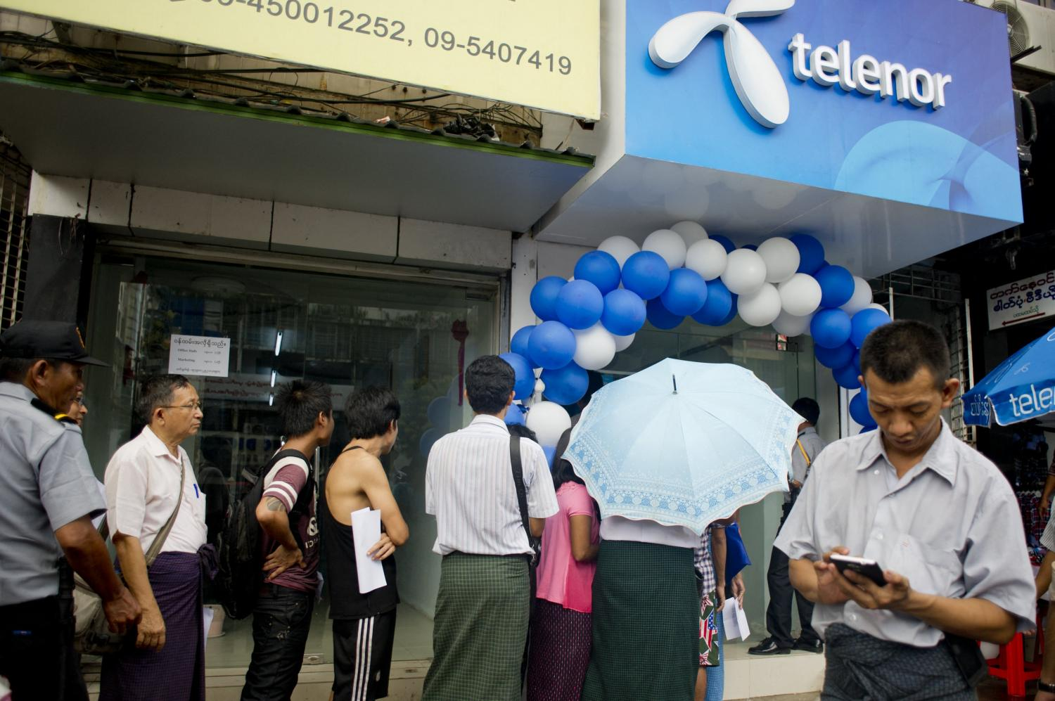 This file photo shows customers queue to buy Telenor sim cards at a mobile shop in Yangon.(AFP photo)