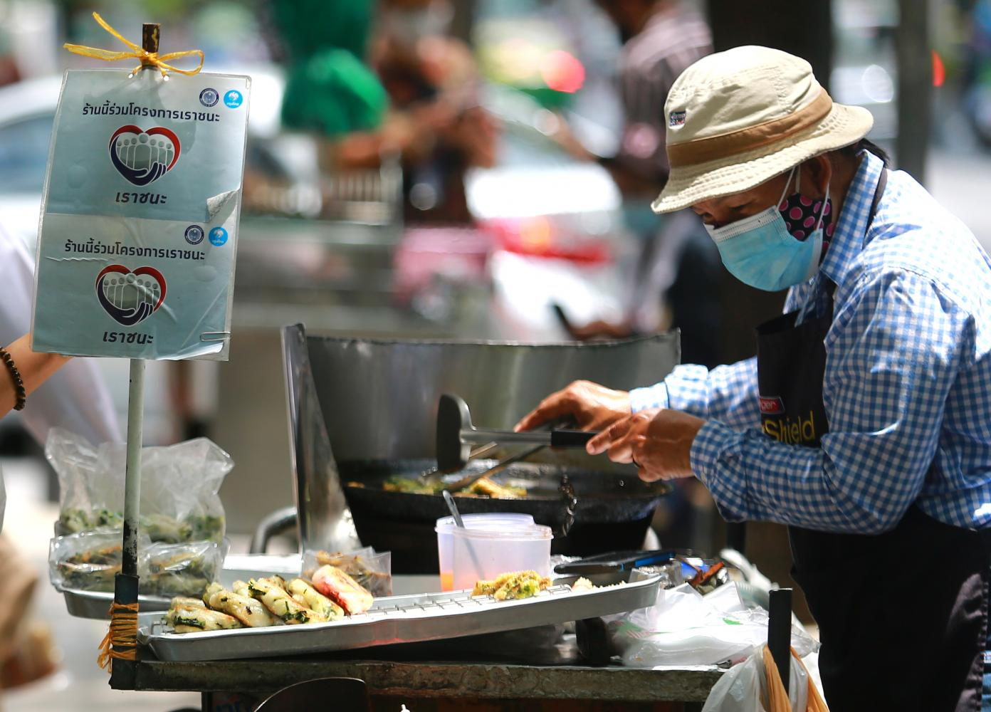 A sign for the Rao Chana (We Win) scheme is displayed at a food stall in the Silom area of Bangkok. Somchai Poomlard