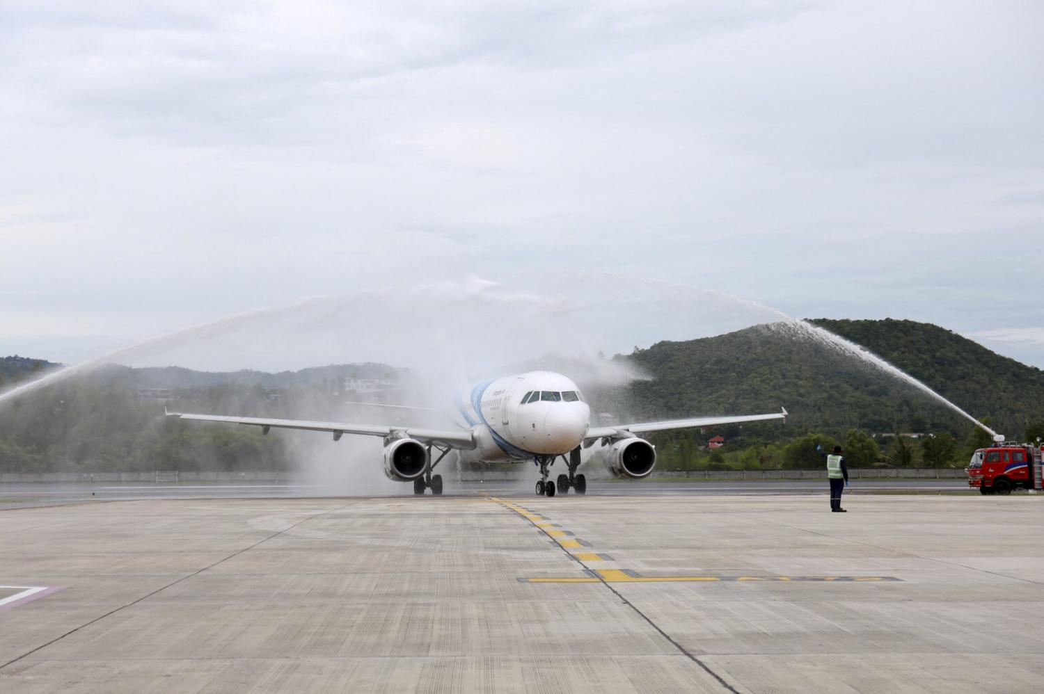 Fire engines spray water on a Bangkok Airways aircraft carrying the first group of foreign visitors to Koh Samui.(Photo: Supapong Chaolan)
