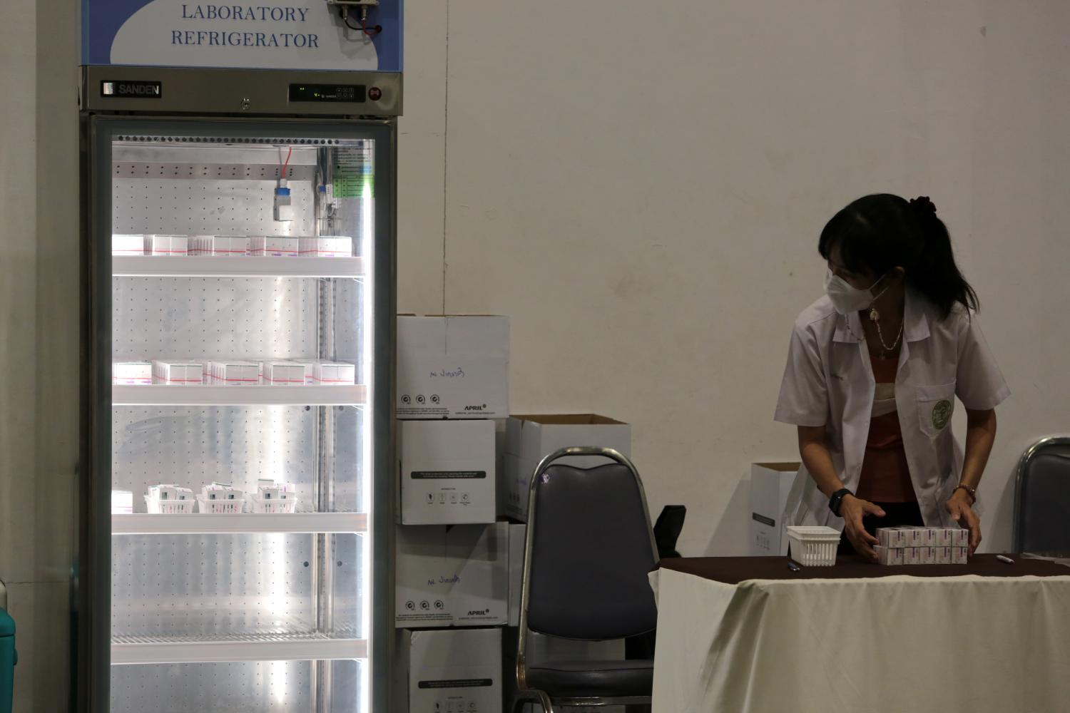 A frontline medical worker at a vaccination site in Nonthaburi province looks at the contents of a refrigerator used for the storage of Covid-19 vaccines.(Photo: Chanat Katanyu)