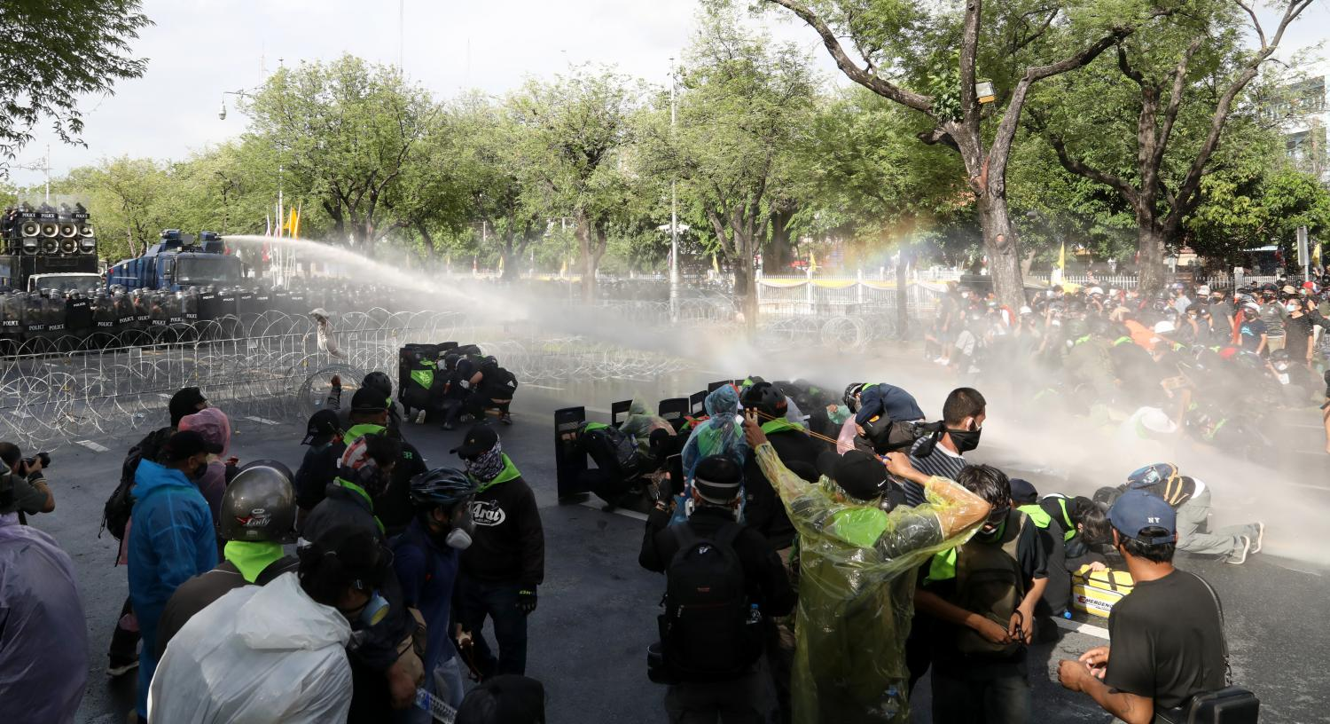 Police spray water at protesters belonging to the Free Youth group during a clash near the Phan Fa intersection on Ratchadamnoen Avenue yesterday. The water cannon was used to deter the protesters as they tried to remove barbed wire during their march to Government House.Arnun Chonmahatrakool