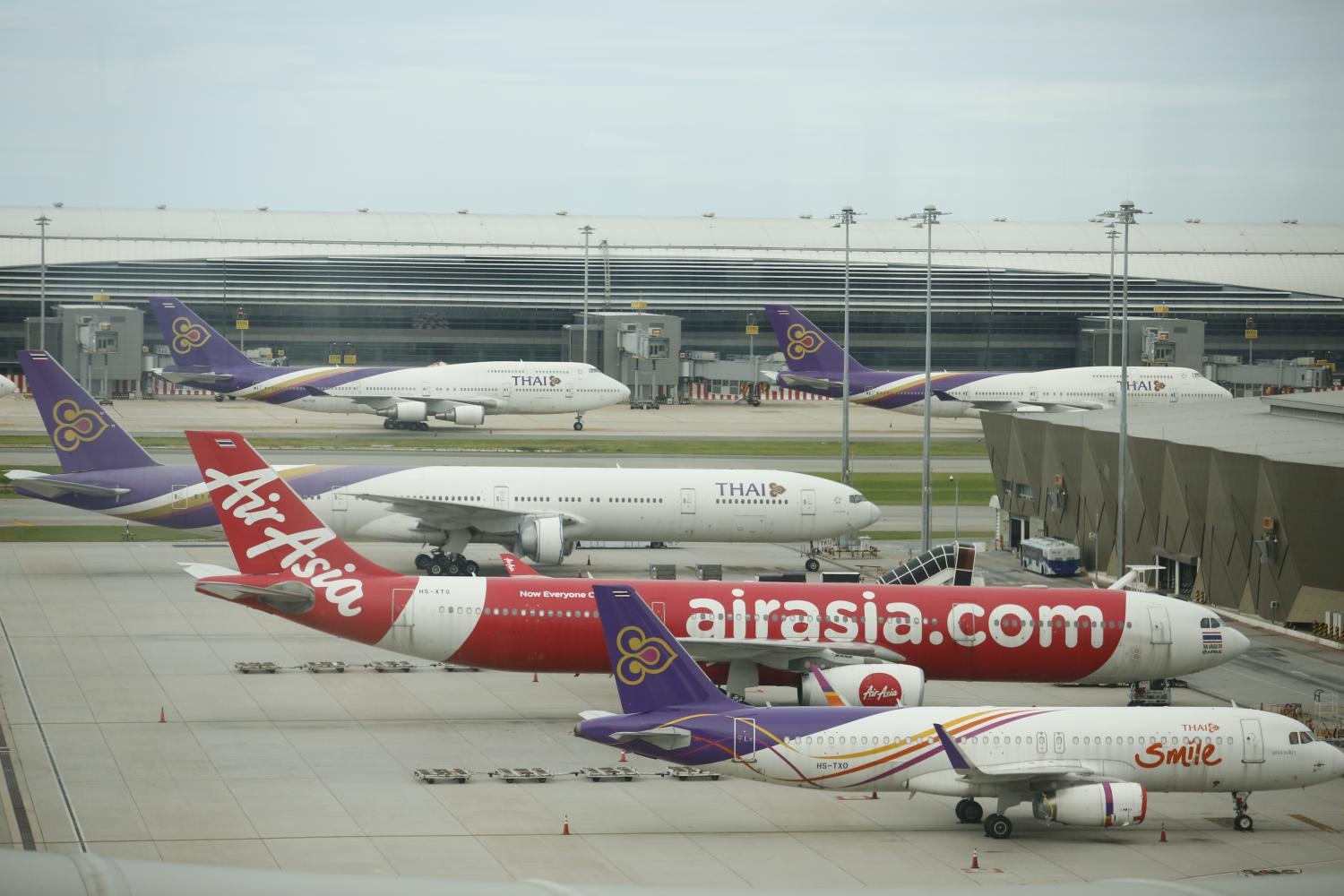 Aircraft belonging to carriers Thai Smile Airways, AirAsia and Thai Airways are seen parked on the tarmac at Suvarnabhumi airport on Monday.Wichan Charoenkiatpakul