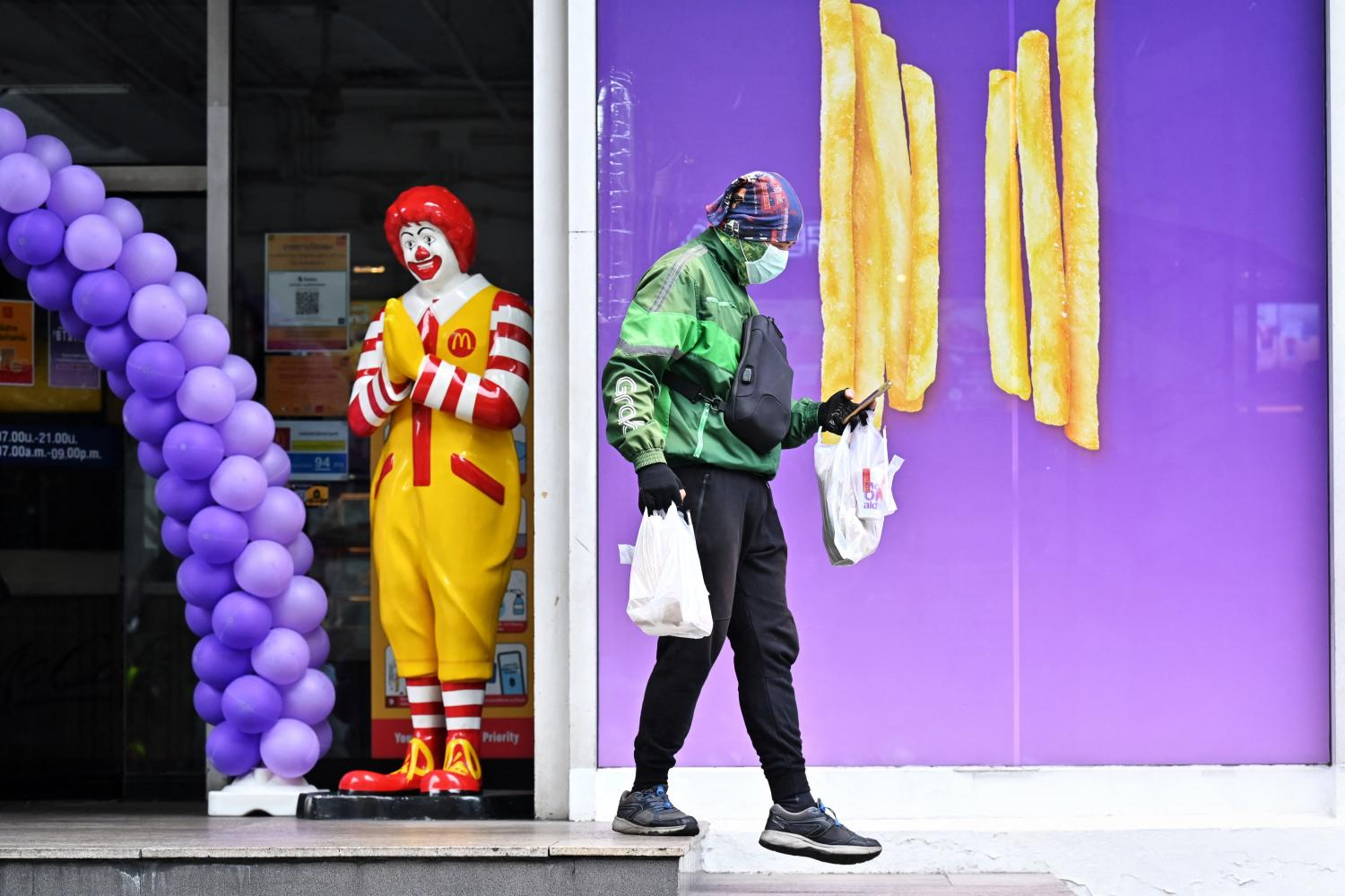 A GrabFood delivery driver picks up orders from a McDonald's branch in Bangkok on Friday, as dine-in bans continue due to Covid-19 restrictions across the country. AFP