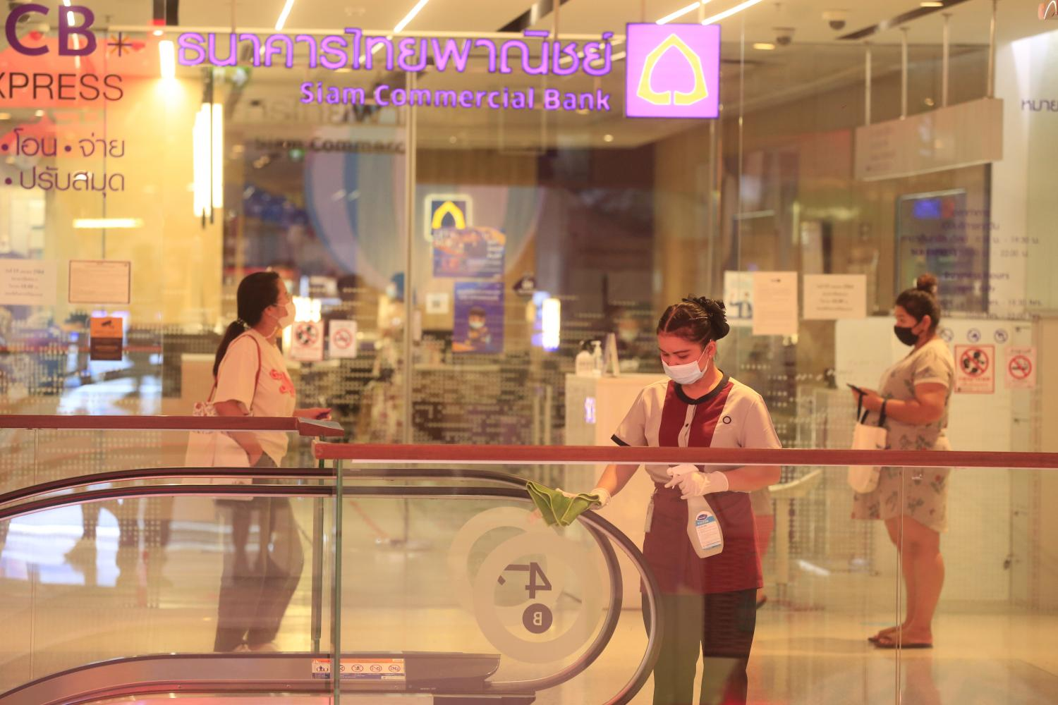A woman walks past Siam Commercial Bank at CentralWorld in Bangkok which is temporarily closed due to the lockdown.Pornprom Satrabhaya