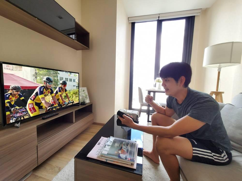 A viewer watches a cycling tournament on television at home with AIS Play. Three channels are being provided for free for everyone via AIS Play.