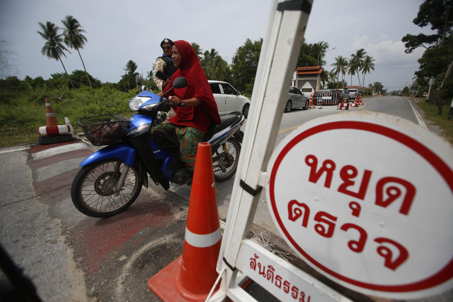 A motorist drives through a security checkpoint set up along a road in Pattani, where many roads in areas which are prone to unrest are under heavy surveillance. Pornprom Satrabhaya
