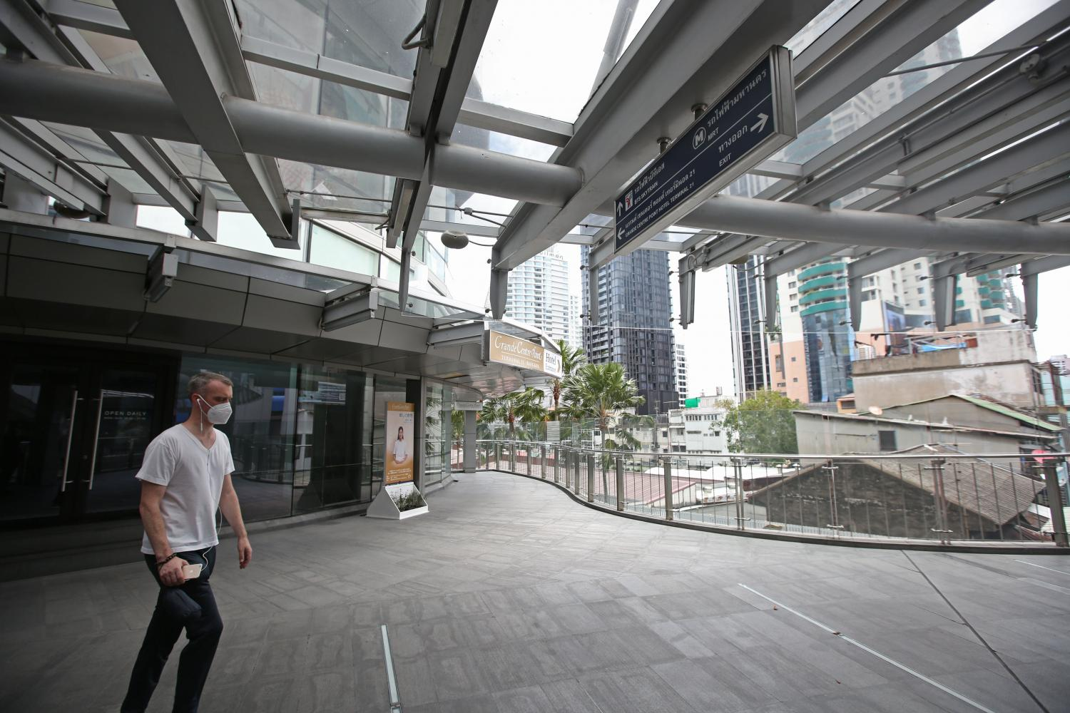 A man walks along the skywalk in front of Terminal 21 mall on Sukhumvit Road, which is nearly empty during the lockdown to curb the spread of the coronavirus.(Photo: Varuth Hirunyatheb)