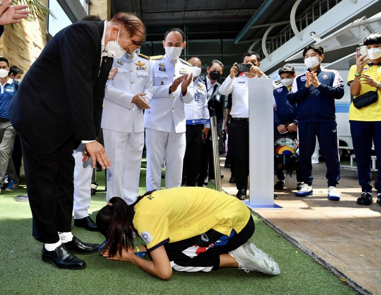 Olympic gold medallist Panipak Wongpattanakit prostrates in front of her father in Phuket as she arrives home following her win in Tokyo. Left Panipak shows off her gold medal as she waves from a Phuket bus. Photos by Phuket public relations office